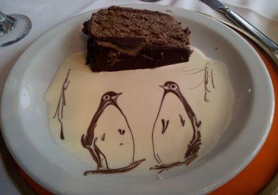 Com calda de chocolate e creme de leite, faz se brotar dois pinguins para acompanhar a torta de chocolate.