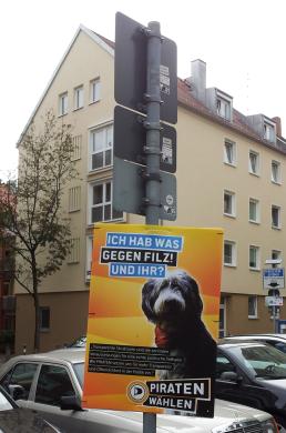 """Em Nuremberg, Alemanha, cartaz eleitoral do Piratas afirma: """"Nós os PIRATAS estamos comprometidos com uma maior transparência e participação pública na política."""" Cartaz da campanha não traz o rosto de nenhum candidato, mas sim de um simpático cachorro. Foto de Chico Sant'Anna."""
